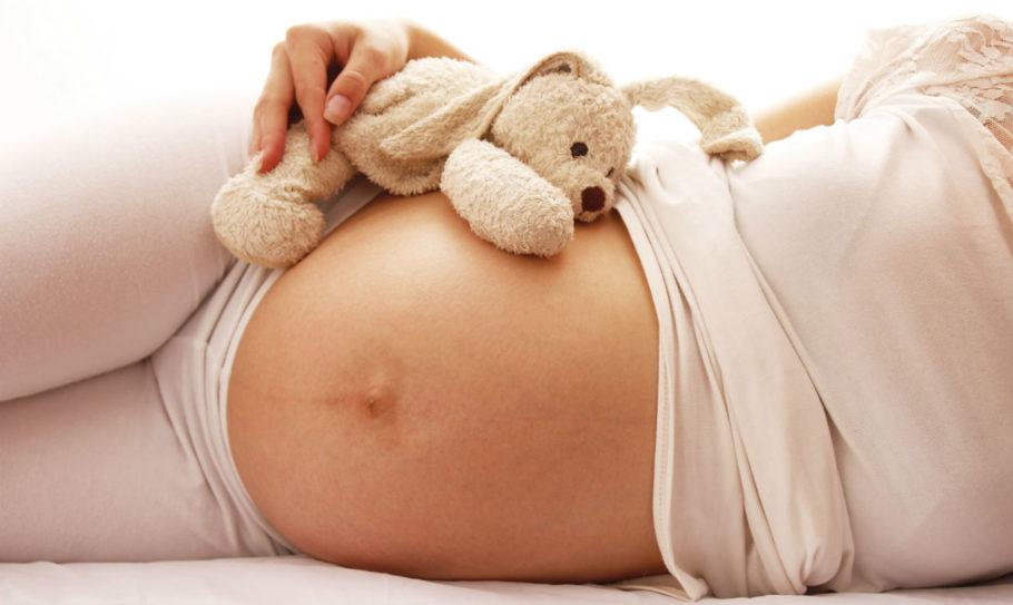 Животик беременной девушки с плюшевой игрушкой