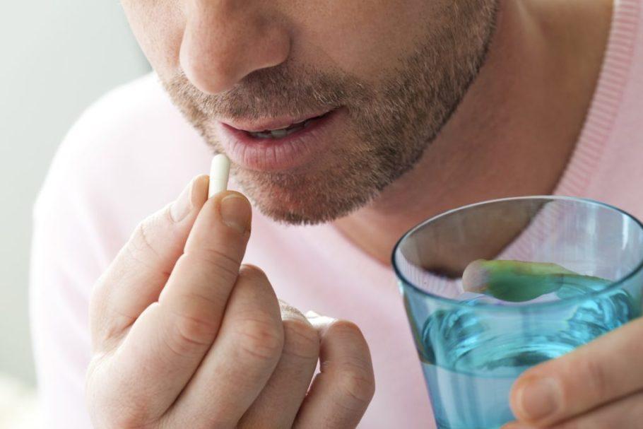 мужчина с таблеткой и стаканом воды