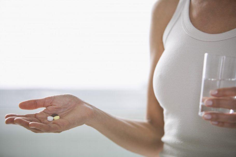 Девушка держит в руках таблетки и стакан
