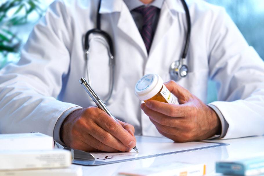 Доктор ведет записи держа упаковку таблеток в руках
