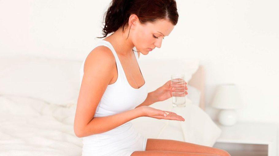 Девушка держит в руках таблетки и стакан с водой