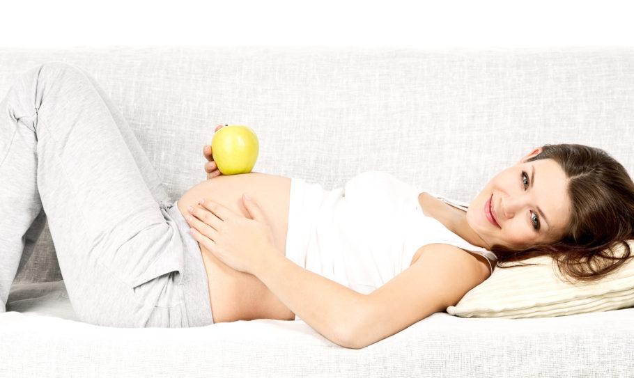 Беременная девушка лежит с яблоком на животике