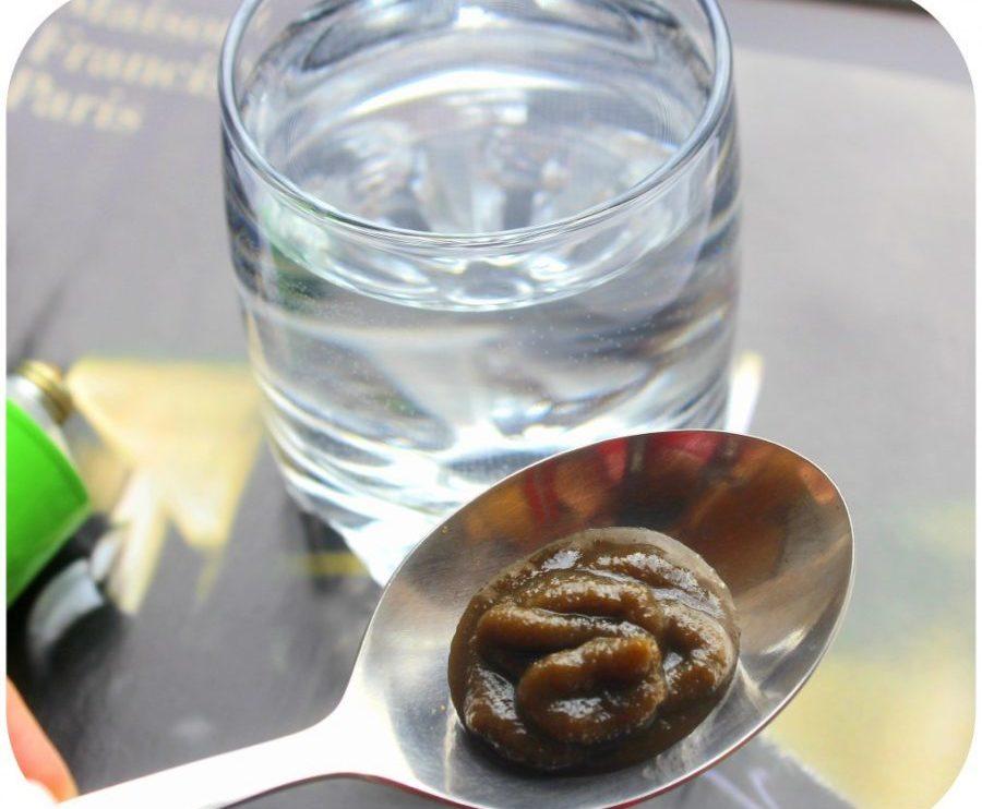 фитолизин на ложке рядом со стаканом с водой