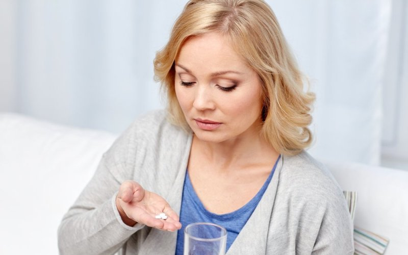 женщина готовится выпить таблетки