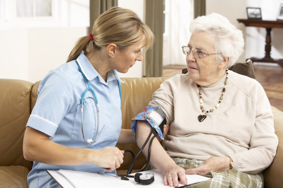 Доктор меряет давление пожилой пациентки