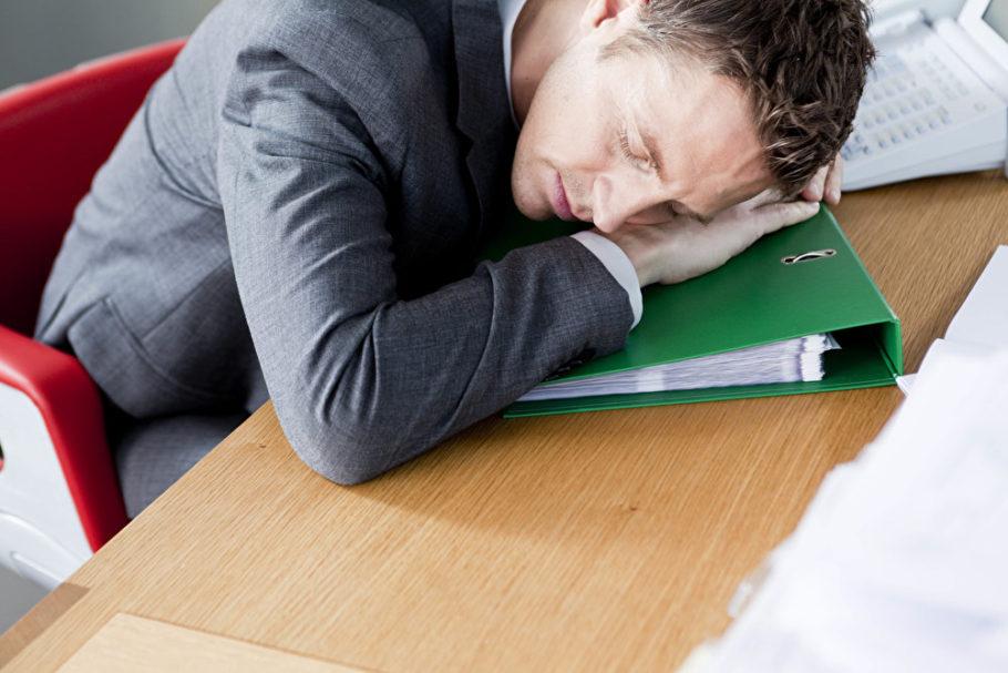 Мужчина уснул на папке на столе