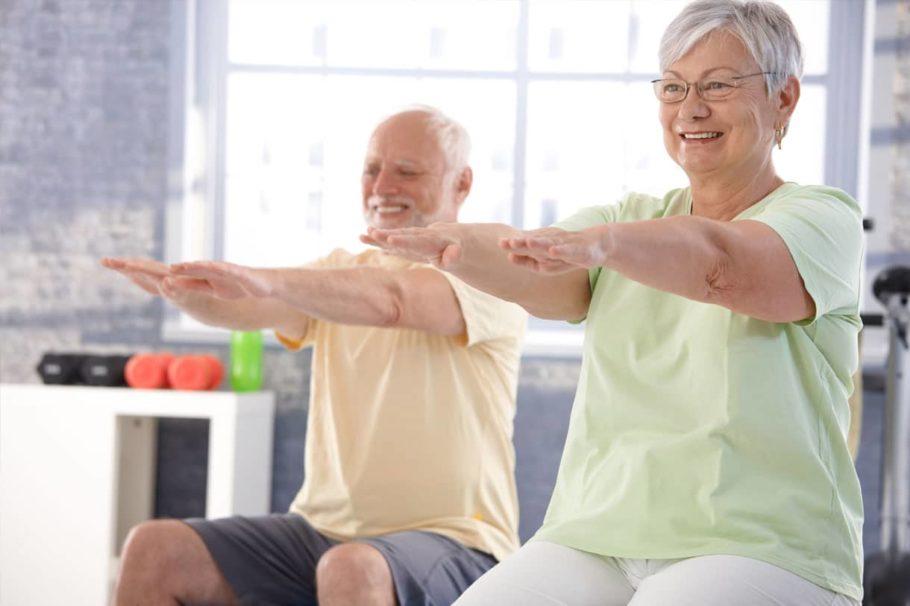 Пожилые мужчина и женщина выполняют упражнения сидя