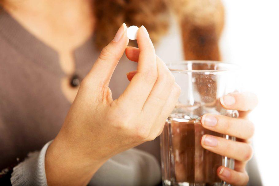 женщина держит в руках таблетку и стакан воды