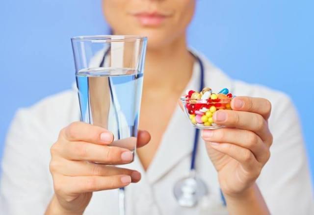 Врач держит стакан с водой и много разных таблеток