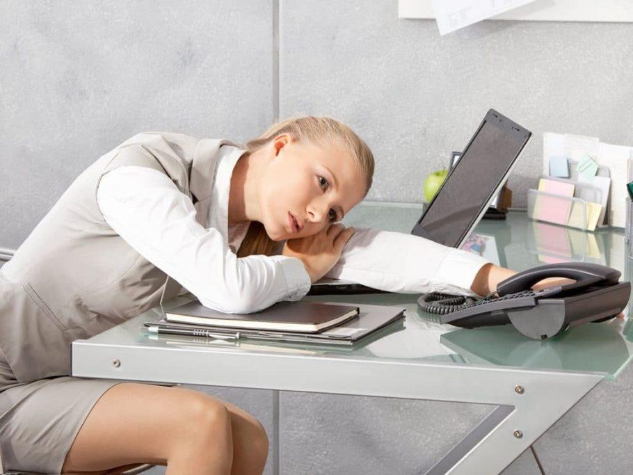 женщина склонилась сидя за столом