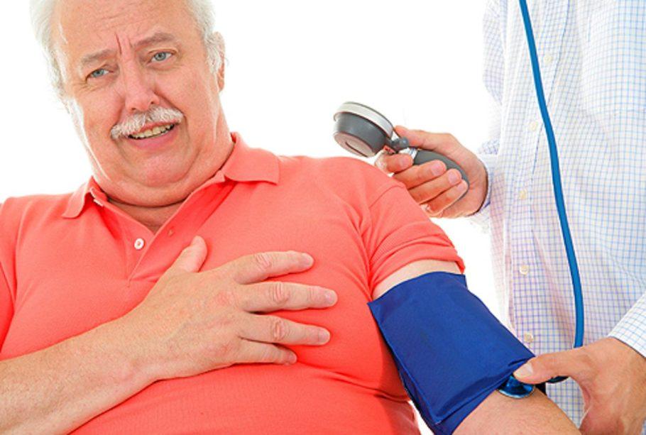 мужчине измеряют давление на руке