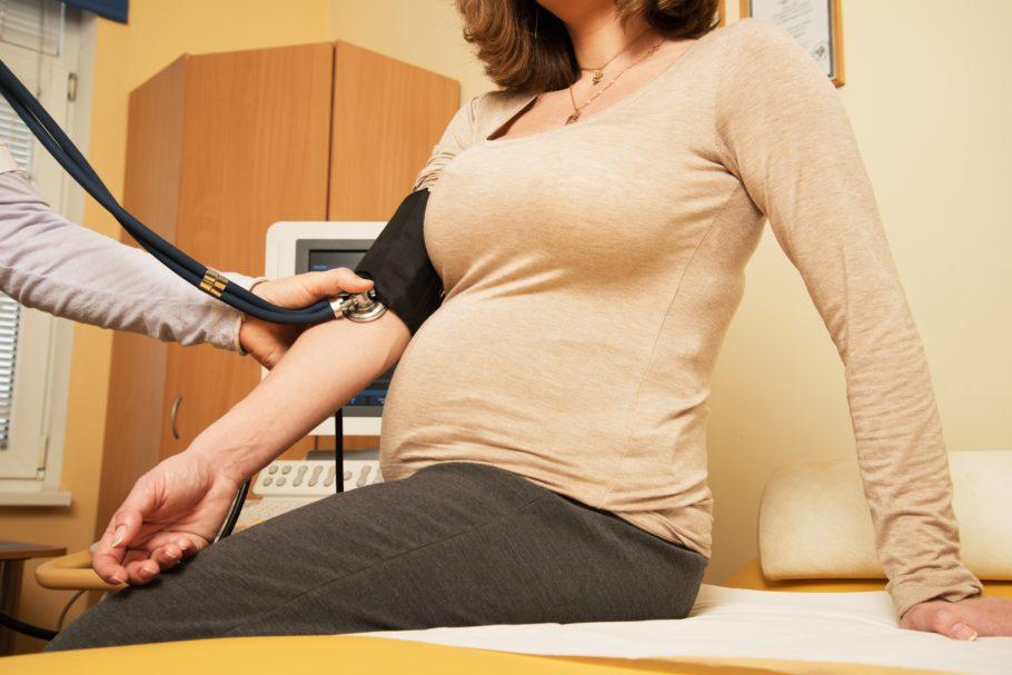 Доктор меряет давление беременной женщине