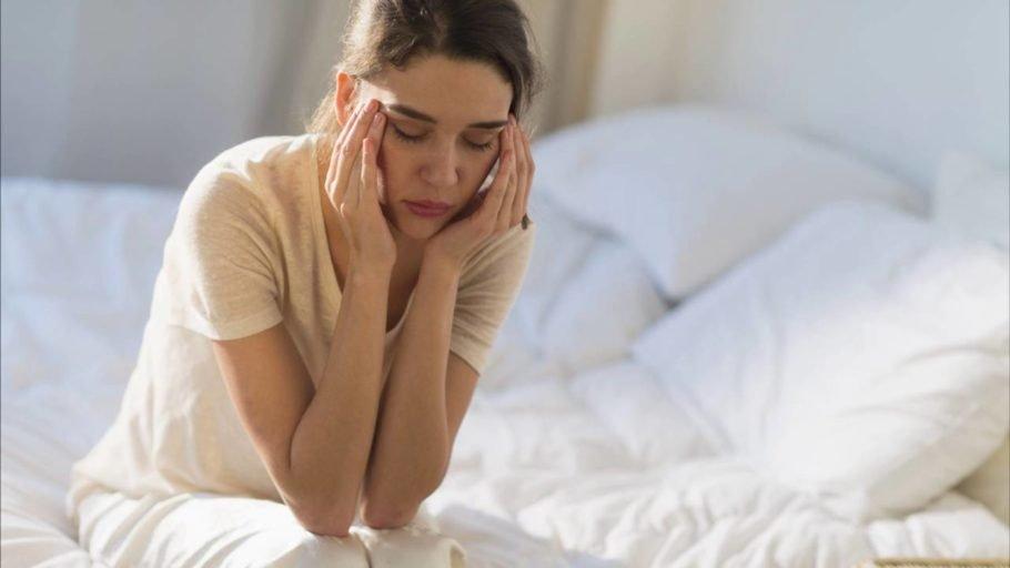 Женщина мыдя на кровати мучается головной болью