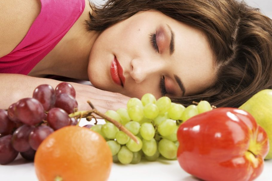 Девушка спит перед виноградом и яблоком
