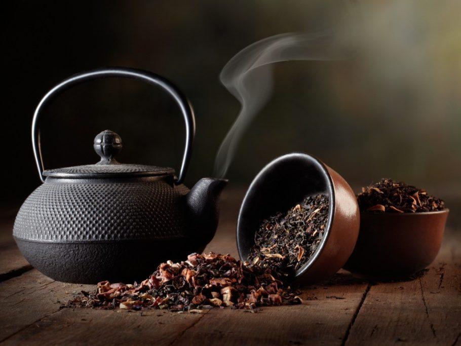 Заварник для чая и просыпанный чай на столе