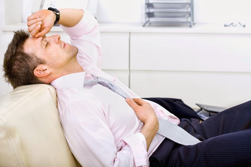 Мужчина устал и полулежит на диване