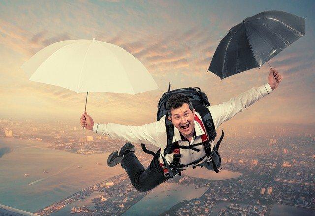 Мужчина летит на двух зонтах