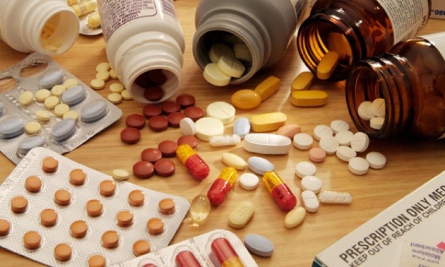 Разные таблетки и капсулы рассыпанные на столе