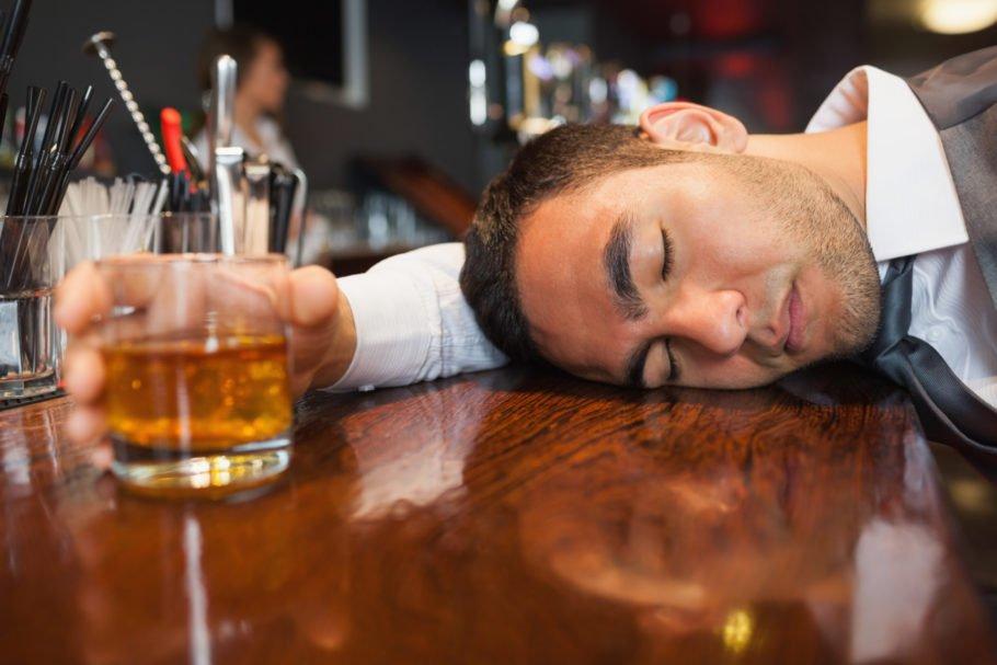 Мужчина уснул на столе со стаканом в руке