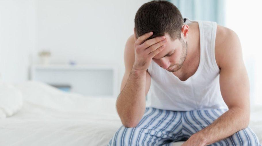 мужчина держится за голову сидя на кровати