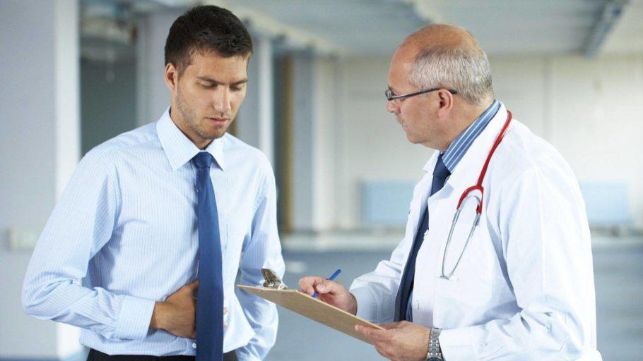 мужчина жалуется врачу на боль в животе