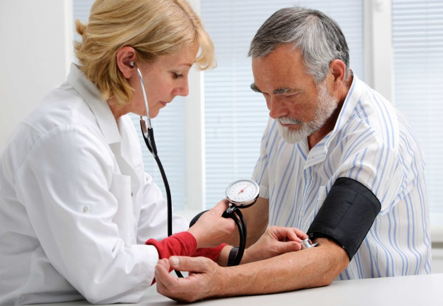 Доктор меряет мужчине давление