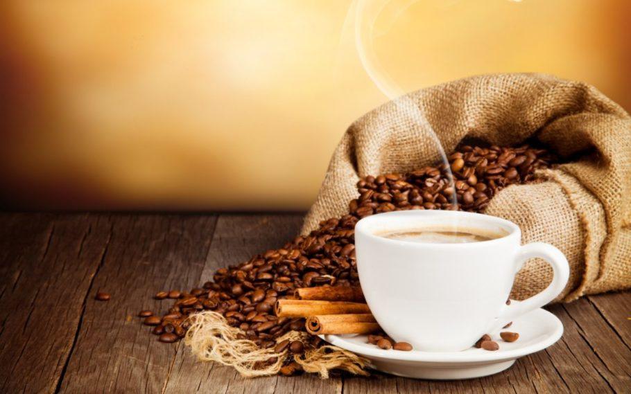 Чашка кофе и просыпанные зерна из мешочка