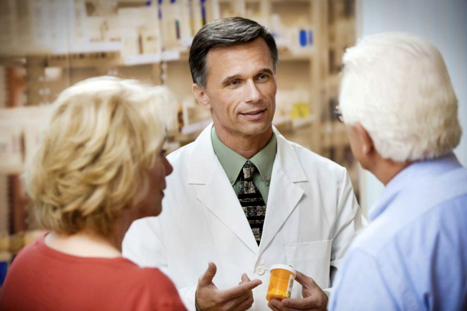 врач показывает мужчине с женщиной таблетки