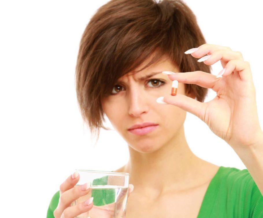 Девушка в зеленом держит капсулу и стакан с водой