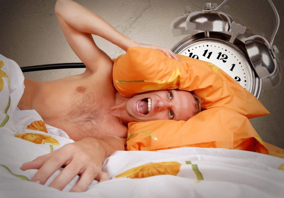 мужчина закрывает уши подушками