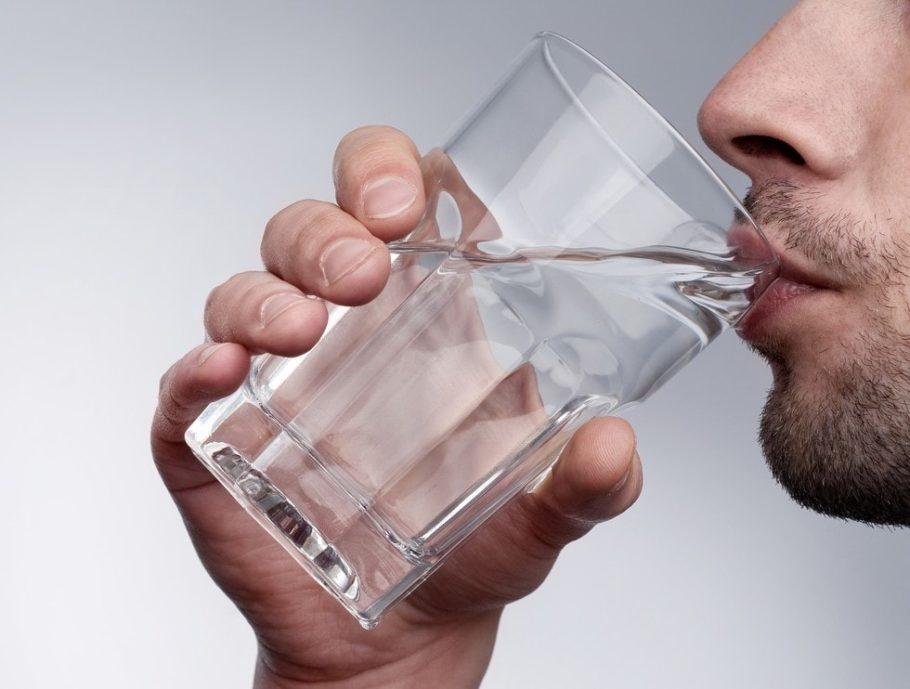 мужчина пьет воду из стакана