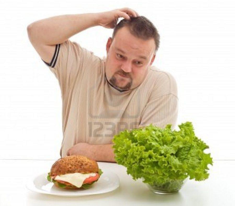 мужчина чешет затылок сидя перед едой