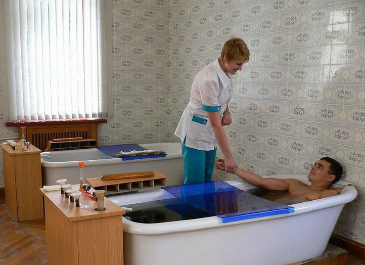мужчина лежит в лечебной ванне возле врача