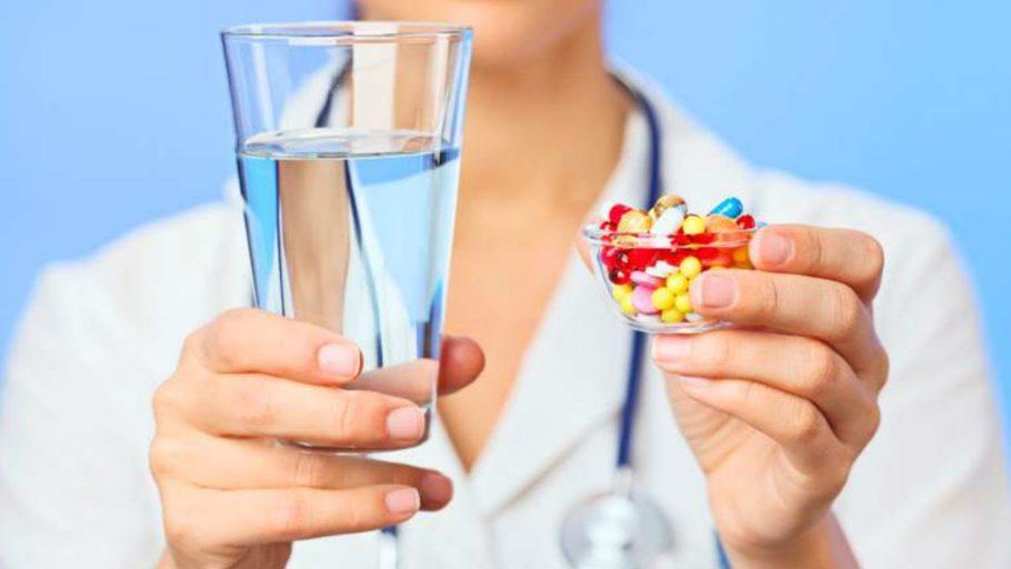 врач держит в руках таблетки и стакан воды