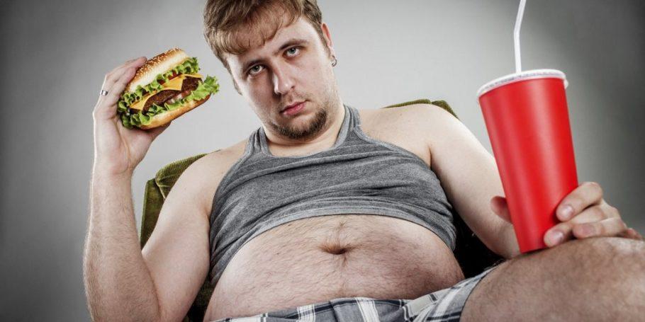 Мужчина с гамбургером в кресле
