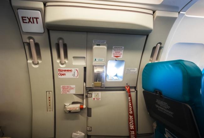 Поручни рядом с аварийным выходом в самолете