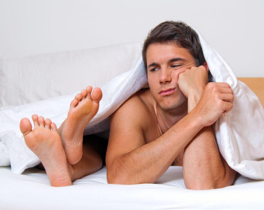 мужчина смотрит на женские ноги под одеялом