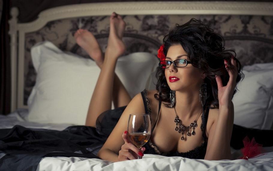 девушка в очках с бокалом на кровати