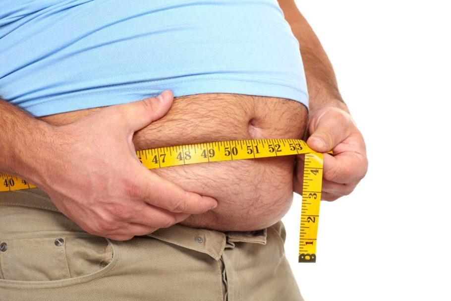 мужчина измеряет объем живота
