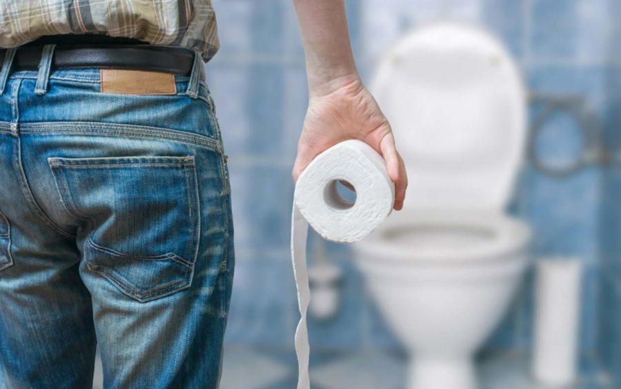 Мужчина в туалете с рулоном бумаги в руках