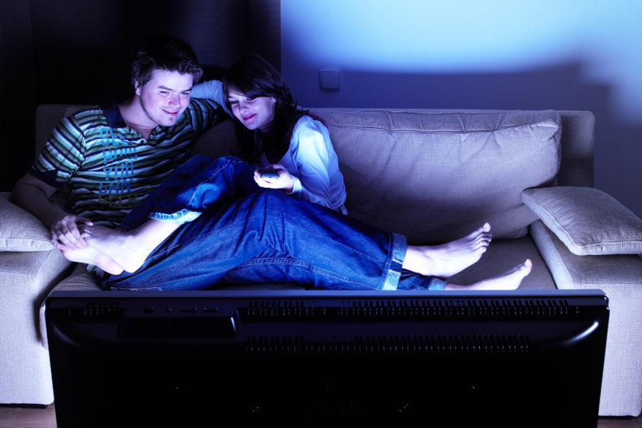 парень и девушка вместе смотрят телевизор