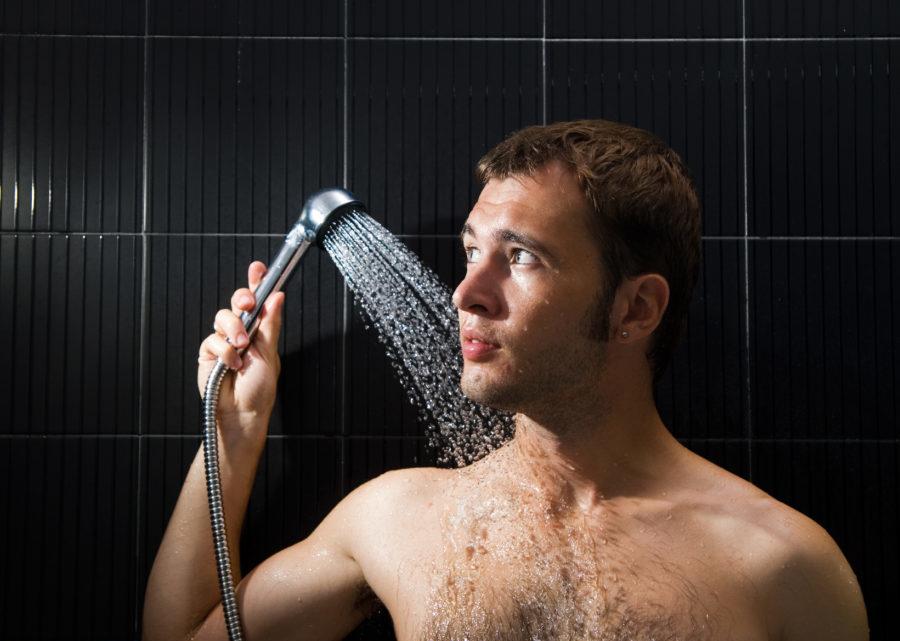 Мужчина поливает себя с лейки в душе