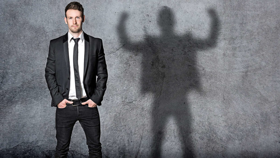мужчина стоит на фоне серой стены