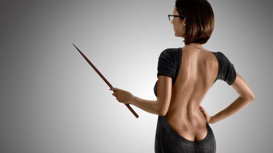 девушка в платье с глубоким вырезом на спине держит указку