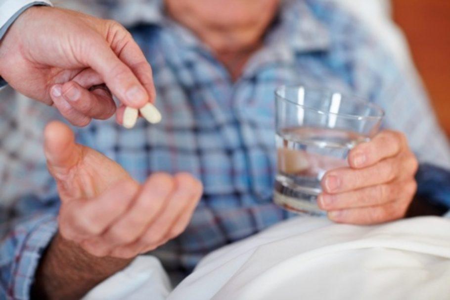 таблетки и стакан воды в руках мужчины