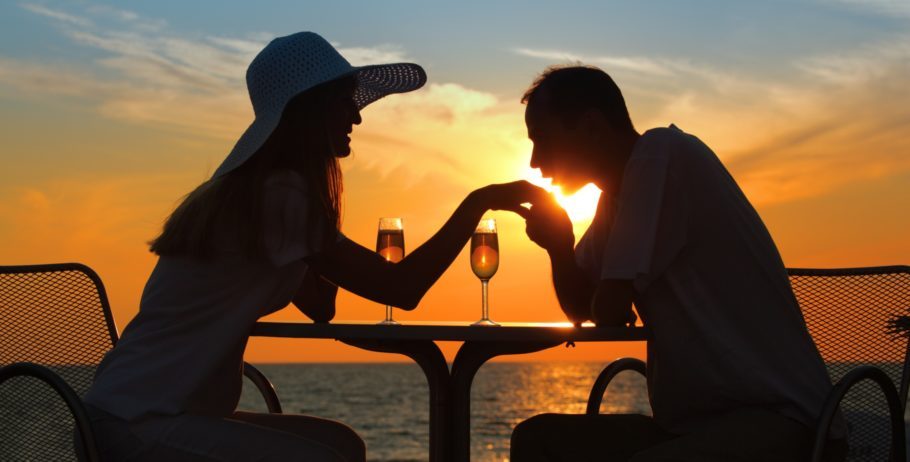 Парень целует девушке руку на фоне заката