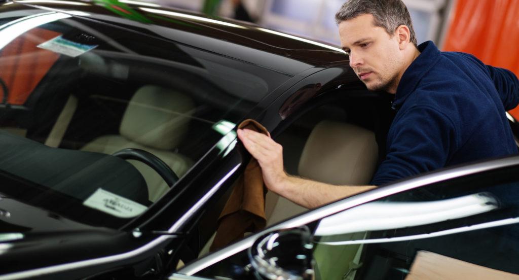 Мужчина полирует автомобиль