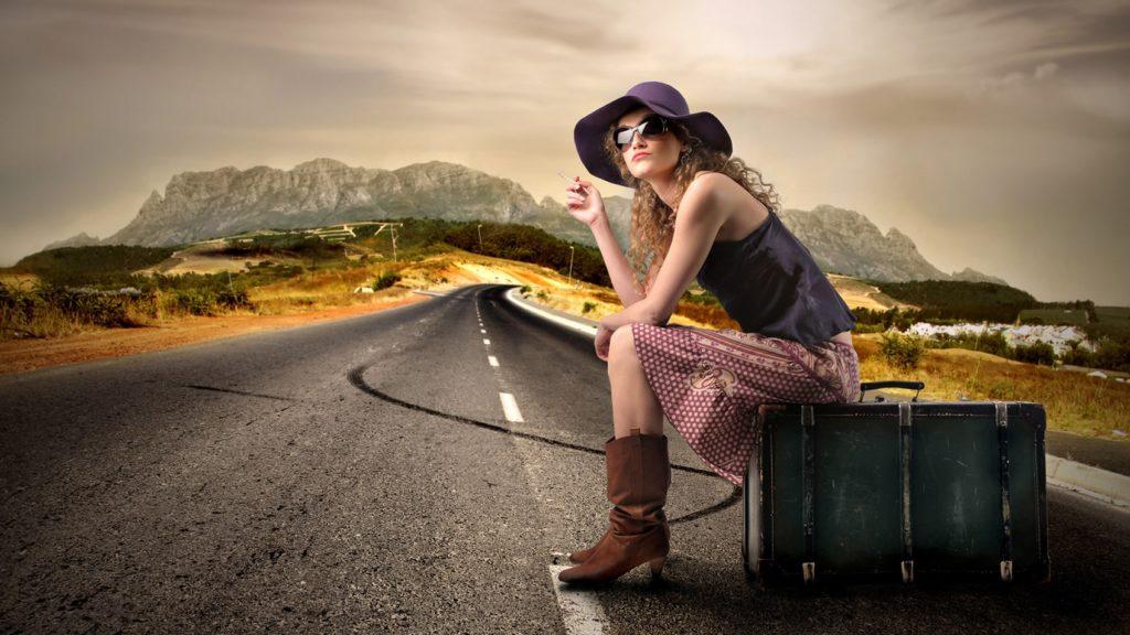 Девушка на чемодане посреди дороги