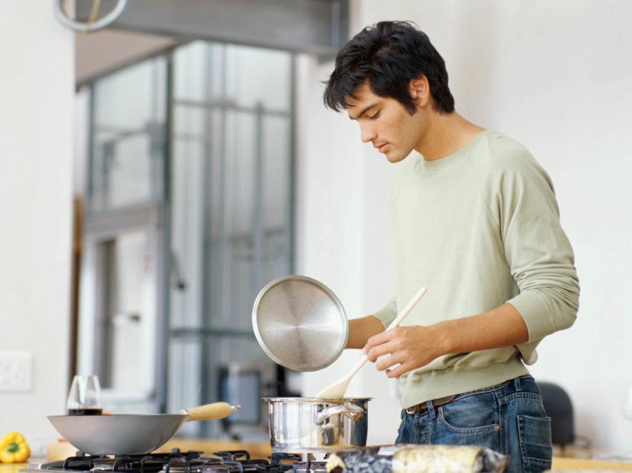 Мужчина готовит у плиты