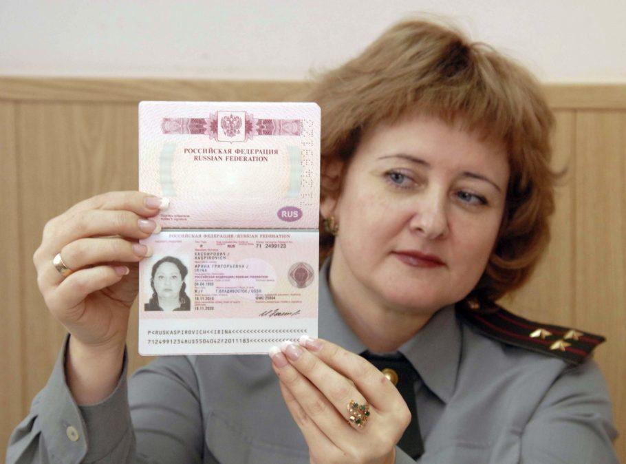 офицер держит раскрытый паспорт